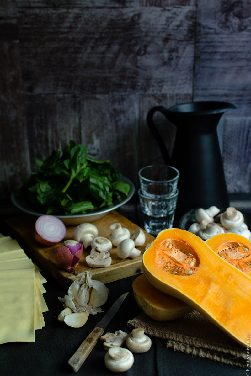 Cottage Cheese Vegetable Lasagne with Butternut Squash, Spinach and Mushrooms www.thefoodiecorner.gr Photo description: An ingredient shot, with the main stars of the dish laid out on a dark surface. A bowl of chopped spinach is in the background, some empty wine glasses next to it and a small bowl of raw mushrooms is to their right, in front of a black jug. To the right of the photo is a cut butternut squash lying face up. In the centre is a chopping board with a halved onion and chopped mushrooms on it. To the left are some sheets of lasagne and a broken up head of garlic. To the front are some more mushrooms and a small knife with a wooden handle.