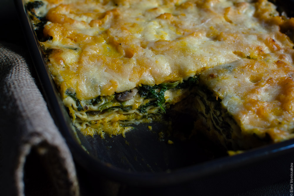 Cottage Cheese Vegetable Lasagne with Butternut Squash, Spinach and Mushrooms www.thefoodiecorner.gr Photo description: A close view of the cooked lasagna in the dish with a piece missing, thus making the inside layers visible.