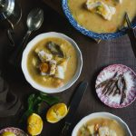 Orange and Lemon Fish Soup with Cod. My version of Greek Psarosoupa. www.thefoodiecorner.gr Photo description: Top view of two bowls of soup, plus one larger serving bowl with a soup ladle in it. The soup is thick and there are vegetables and pieces of fish protruding from within. To the right is a small plate with anchovies, to the bottom left a small plate with two halves of a lemon. There are also pieces of orange, slightly squeezed, near the plate of lemons, and a knife with a wooden handle. Scattered around are some celery leaves. Towards the top left are a couple of soup spoons and a metal olive oil jug, and at the top in the centre are some more orange pieces on a wooden chopping board. Everything is on a dark wooden surface.