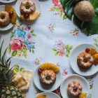 Greek Ravani Turned Mini Pina Colada Cakes www.thefoodiecorner.gr Photo description: Mini bunt shaped ravani cakes on small white plates sitting on a white surface. The cakes have a sprinkling of coconut flakes on them, two small pieces of pineapple at the side and one red cherry. Some of the plates are on a narrow white tablecloth with colourful flowers on it. The plates are mainly placed in the top left and bottom right corners. Top right are two coconuts on a big leaf and bottom left is a pineapple on a bright coloured tea towel.