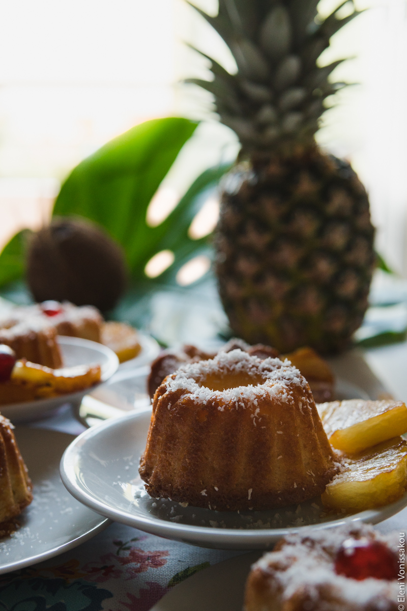 Greek Ravani Turned Mini Pina Colada Cakes www.thefoodiecorner.gr Photo description: A side view of a cake, its plate sitting on top of other plates. A whole pineapple is visible against a bright background, as is part of a monstera leaf.