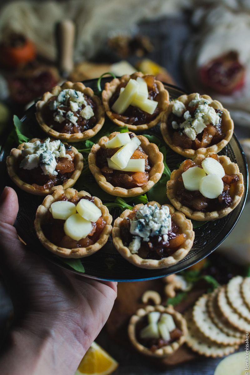 Savoury Tarts with Pear Chutney and Blue Cheese or Gruyere www.thefoodiecorner.gr Photo description: A hand entering the frame from the left side, holding a plate of tarts. Barely visible in the background is the rest of the cheese board.