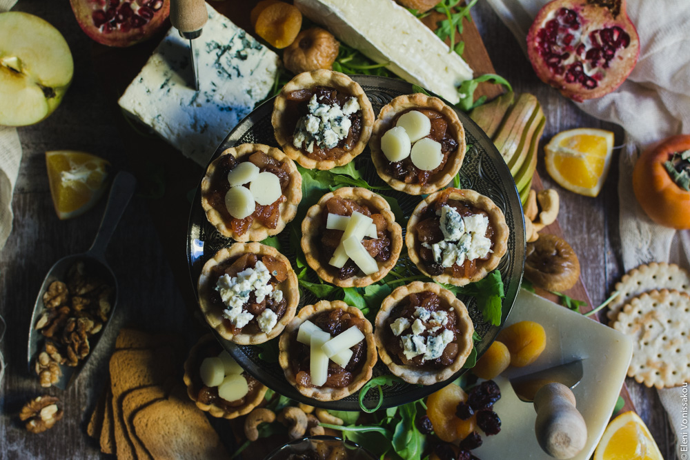 Savoury Tarts with Pear Chutney and Blue Cheese or Gruyere www.thefoodiecorner.gr Photo description: a top view of the tarts laid out on the cake stand in the middle of the cheese board. Around it are crackers, pieces of orange, pomegranate, gruyere cheese, blue cheese, brie, dried apricots and figs, walnut pieces, half an apple and a persimmon barely visible.