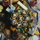 Savoury Tarts with Pear Chutney and Blue Cheese or Gruyere www.thefoodiecorner.gr Photo description: A wooden serving board filled with various cheeses, dried fruits, oranges, pears, persimmons, a cut pomegranate, nuts and crackers. In the centre is a cake stand with some savoury tarts on it. The edges of the tarts are fluted, they are filled with chutney and on top there are some pieces of gruyere or crumbled blue cheese. Barely visible under all the nibbles are some rocket (arugula) leaves.