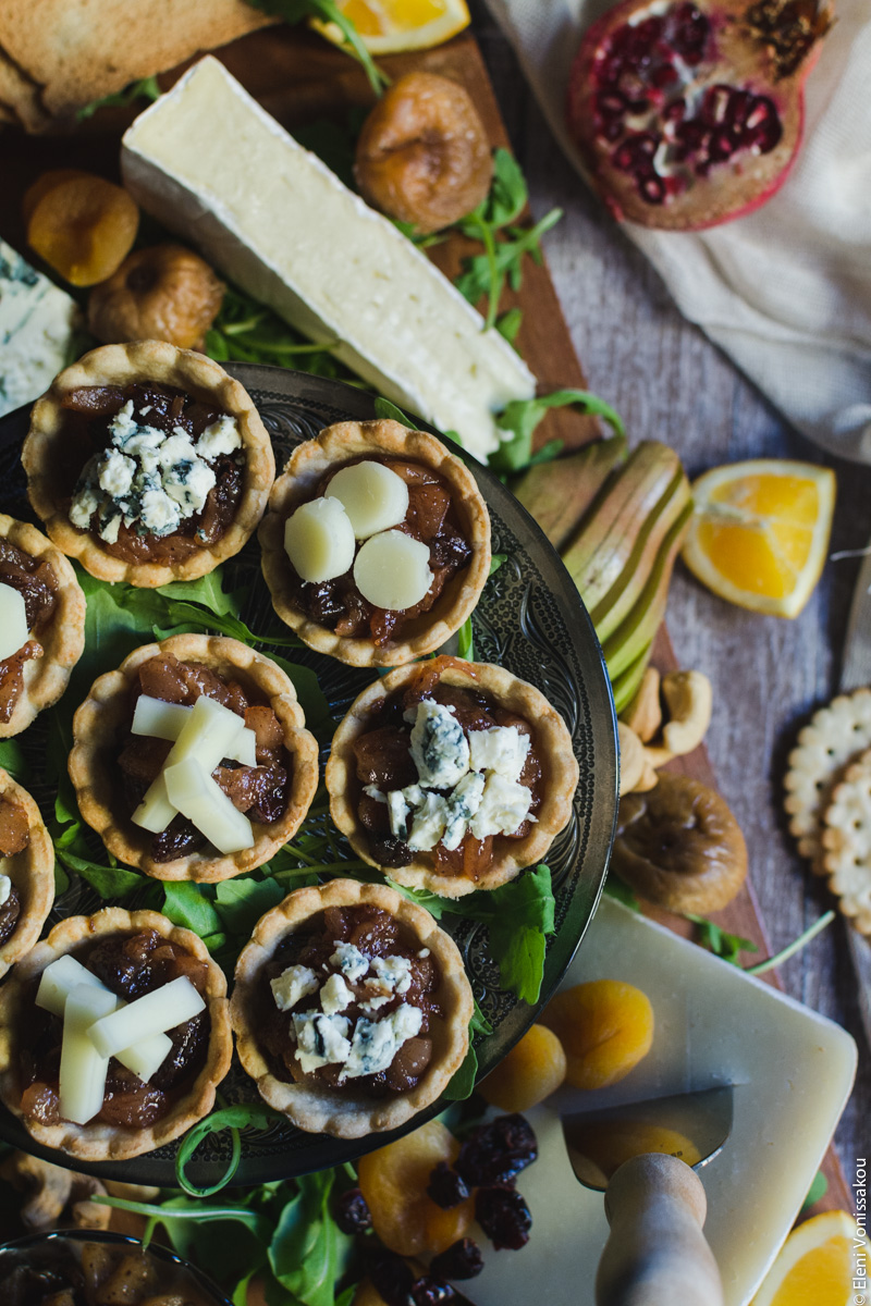 Savoury Tarts with Pear Chutney and Blue Cheese or Gruyere www.thefoodiecorner.gr Photo description: a closer top view of the tarts, some of them cut out of the photo on the left. In the background to the bottom of the photo is a piece of gruyere with a knife in it, and to the top, a piece of brie. Some fruit and crackers are also scattered around the tarts.