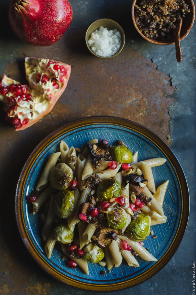 Pasta with Balsamic Roasted Brussels Sprouts and Shiitake Mushrooms (Vegan) www.thefoodiecorner.gr Photo description: One plate of pasta on a rusty metal surface. To the top, broken piece of pomegranate, a tiny bowl of salt and a wooden bowl with pangrattato.