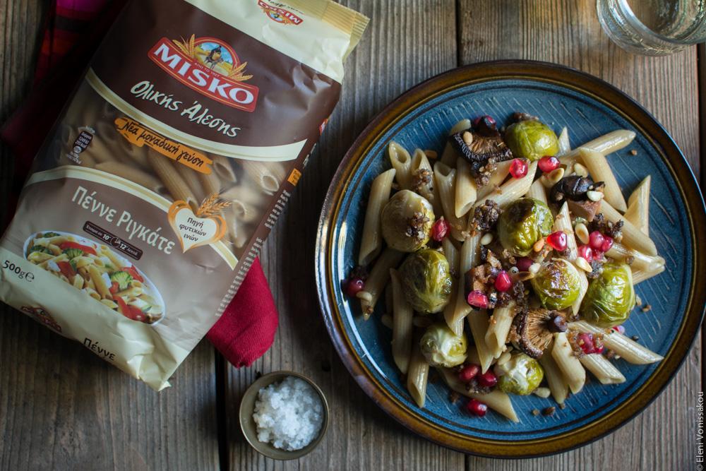 Πέννες Ολικής Άλεσης με Ψητά Λαχανάκια Βρυξελλών και Μανιτάρια Σιτάκε (Vegan) www.thefoodiecorner.gr περιγραφή: Αριστερά μια συσκευασία πέννε ριγκάτε MISKO ολικής άλεσης, με μια πετσετούλα να εξέχει λίγο από κάτω της. Δεξιά ένα πιάτο με πέννες, λαχανάκια, μανιτάρια και ρόδι και ανάμεσά τους ένα πολύ μικρό μπολάκι με αλάτι.
