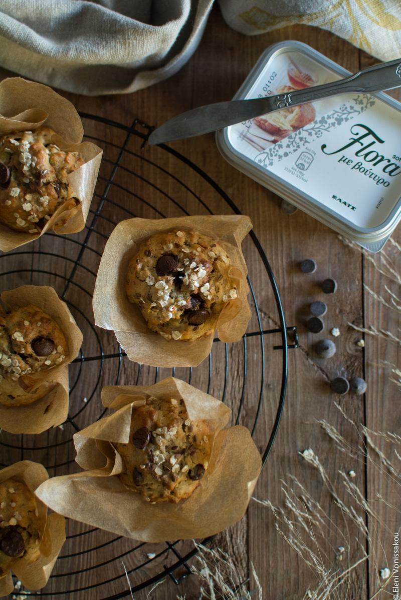 Μάφινς Μπανάνας με Βρώμη, Μέλι, Ταχίνι και Σταγόνες Σοκολάτας www.thefoodiecorner.gr Περιγραφή φωτογραφίας: Έτοιμα ψημένα μάφινς μέσα σε θήκες λαδόκολλας, τοποθετημένα σε στρογγυλή σχάρα. Δεξιά προς τα πάνω, μια συσκευασία μαργαρίνη με ένα μαχαιράκι. Λίγες σταγόνες σοκολάτας είναι σκορπισμένες στην ξύλινη επιφάνεια. Κάτω δεξιά φαίνονται λίγα φύλλα από κάποια διακοσμητικά ξερά χορτάρια.