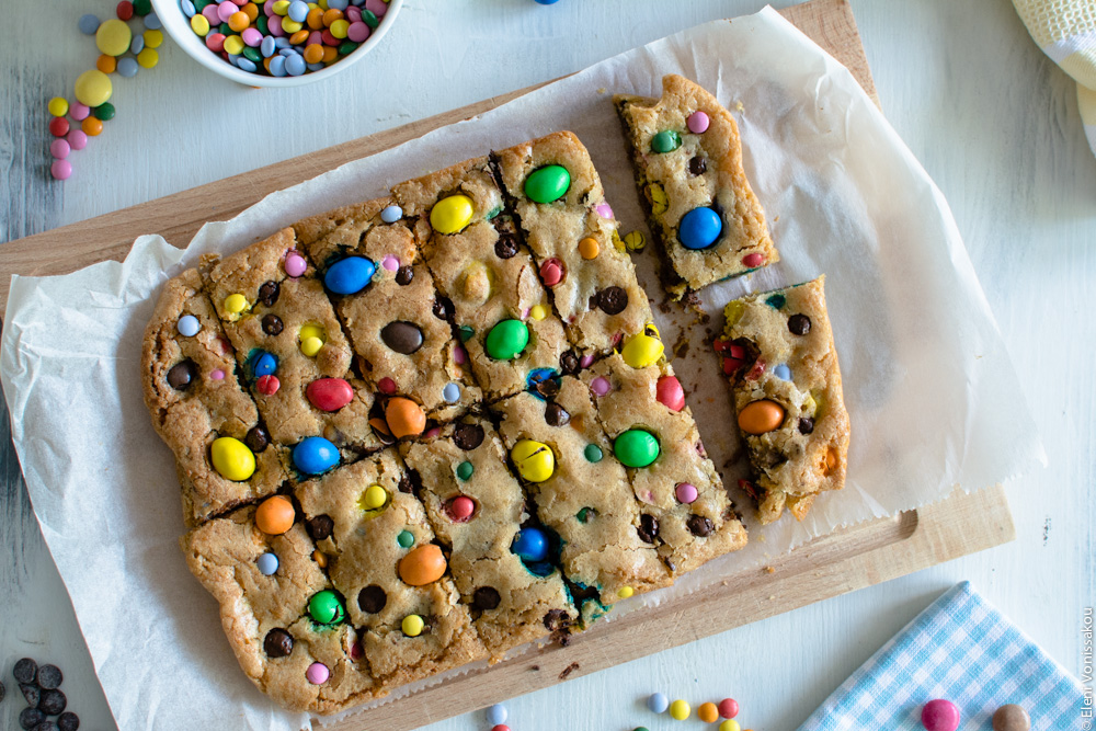 Easy, One-bowl, Colourful Chocolate Chip Cookie Bars www.thefoodiecorner.gr Photo description: A close view of the newly cut cookie bars, still arranged next to each other on the baking paper. The paper is set on a wooden chopping board. The top of the cookies is adorned with colourful chocolate candies.