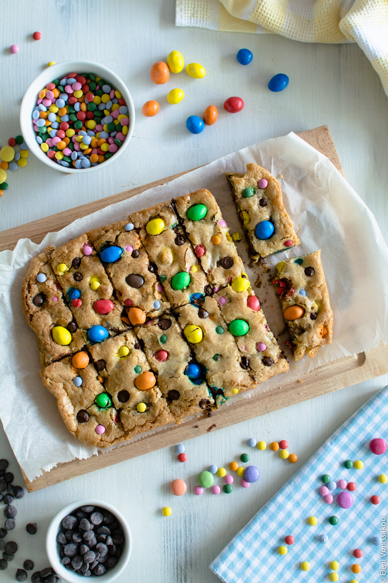 Easy, One-bowl, Colourful Chocolate Chip Cookie Bars www.thefoodiecorner.gr Photo description: The cookie bars on the chopping board, freshly cut but not yet separated. Around the board are some scattered candies on the wooden surface and in a bowl, and some chocolate chips also on the surface and in a small bowl. In the top right and bottom right corners are a couple of colourful, chequred tea towels.