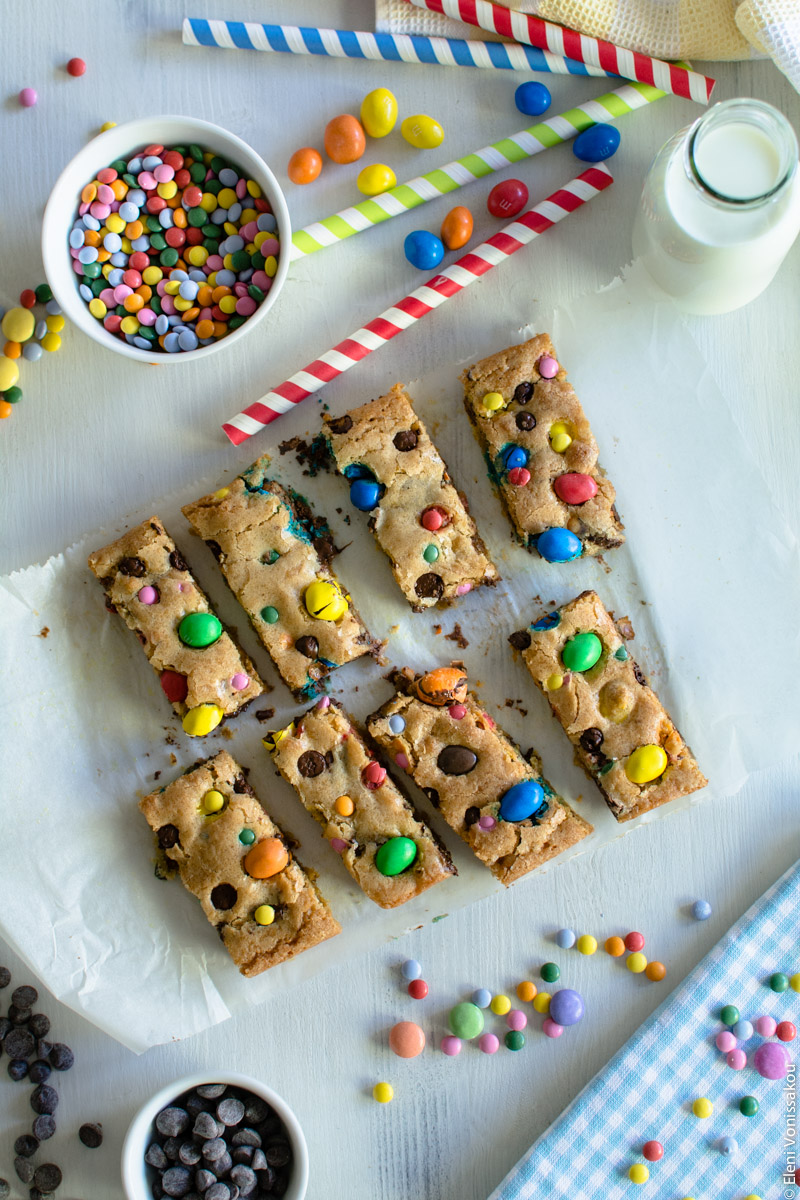 Easy, One-bowl, Colourful Chocolate Chip Cookie Bars www.thefoodiecorner.gr Photo description: Eight cookie bars, arranged in two rows of four, on the baking paper they were baked on. Around them are the scattered candies. In the top right corner is a small glass bottle of milk and some stripy paper straws.