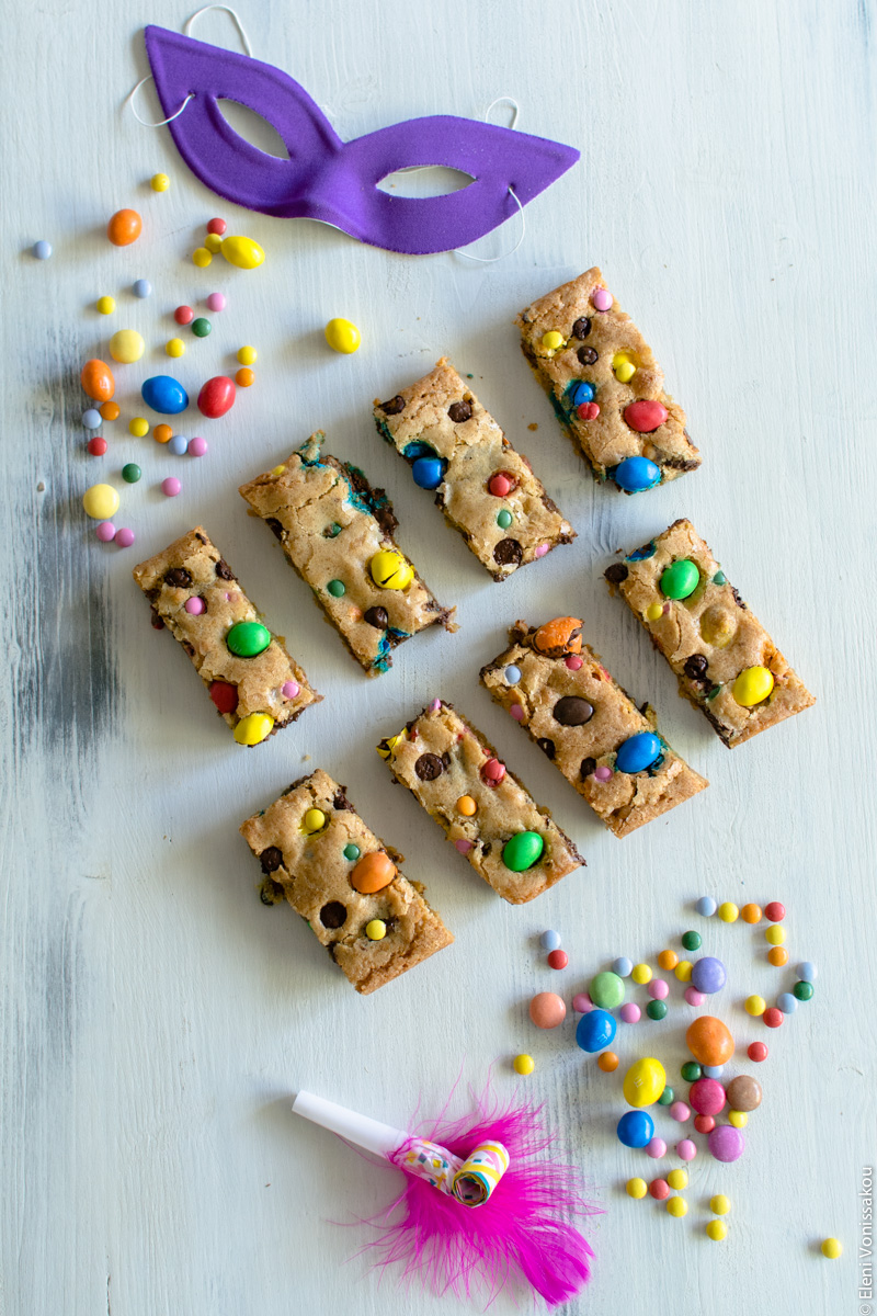 Easy, One-bowl, Colourful Chocolate Chip Cookie Bars www.thefoodiecorner.gr Photo description: Same set up as main photo, but instead of white feathers at the bottom of the photo is a small party horn with a pink feather attached to it.
