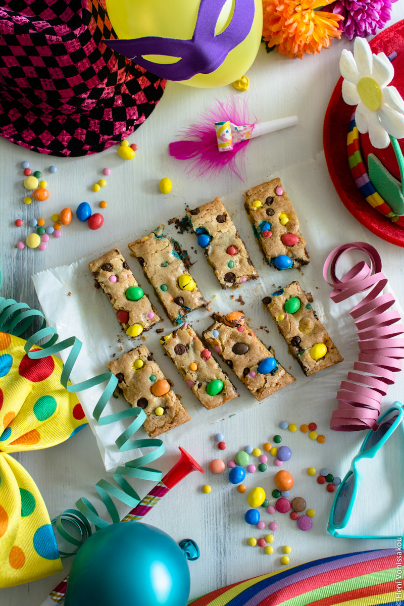 Easy, One-bowl, Colourful Chocolate Chip Cookie Bars www.thefoodiecorner.gr Photo description: The cookie bars are in the centre of the photo surrounded by lots of carnival items. Clockwise from top right, a clown hat with a flower sticking out of it, some paper streamers, a pair of plastic turquoise sunglasses, some stripey material (barely showing), a balloon, a big clown bow tie, a shiny hat, a party horn and a balloon with an eye mask on it.  Around the cookies are some scattered colourful candies too.