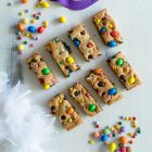 Easy, One-bowl, Colourful Chocolate Chip Cookie Bars www.thefoodiecorner.gr Photo description: Cookie bars with colourful chocolate candies on top. The bars are on a white wooden surface, arranged in two rows of four. To their top left and bottom right are some more candies. Towards the top of the photo in the centre is a purple carnival eye mask, and the bottom left corner of the photo is filled with white feathers.