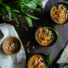 West African Inspired Chicken and Sweet Potato Soup with Peanut Butter www.thefoodiecorner.gr Photo description: Three bowls of thick soup on a wooden surface. To the top left are some fresh beetroot greens, and below that is a linen napkin and a small bamboo bowl of peanuts. At the very top of the photo is a stripy piece of material. In the bottom right corner are some spoons laying on a black tea towel. The soup itself in the bowls has pieces of sweet potato and chicken showing through, and is decorated with chopped peanuts and chopped beetroot leaves.