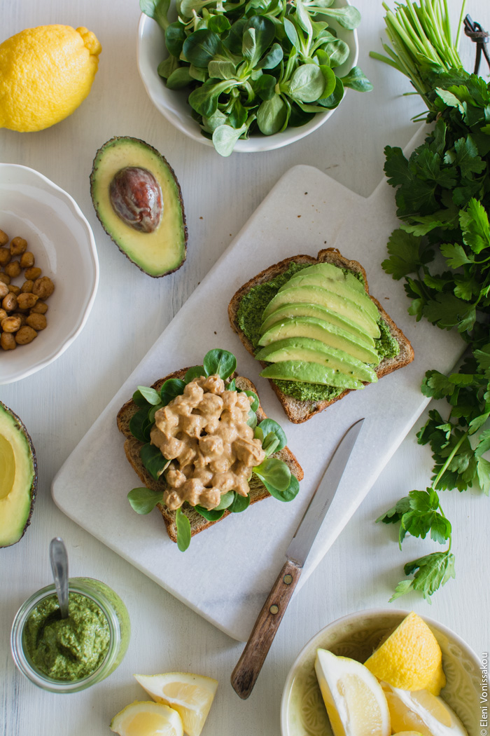 Vegan Chickpea and Tahini Sandwich with Avocado and Parsley Pesto www.thefoodiecorner.gr Photo description: Two slices of bread, one of them spread with parsley pesto and slices of avocado, the other with lamb's lettuce and chickpeas in tahini sauce. Both slices are on a marble cutting board surrounded by more ingredients.