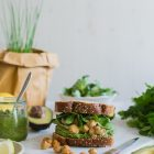 Vegan Chickpea and Tahini Sandwich with Avocado and Parsley Pesto www.thefoodiecorner.gr Photo description: A front side view of a sandwich, stuffed with filling. The sandwich is on a marble cutting board, which in turn is on a white wooden surface. It is surrounded by parsley, avocado, some lemon wedges, a small jar of pesto and a pot of chives in the background.