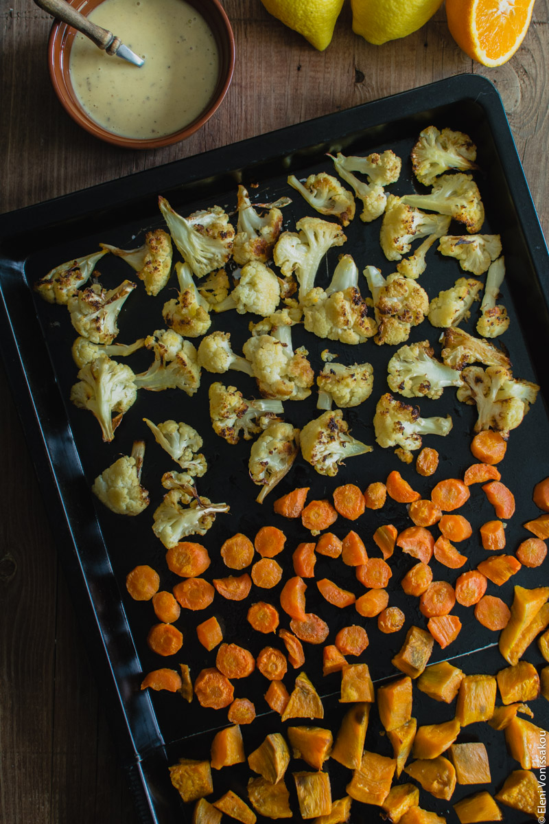 Lenten Bowls with Bulgur Wheat, Beluga Lentils, Roast Veggies and Honey Tahini Dressing www.thefoodiecorner.gr Photo description: A baking sheet with three rows of cubed roasted vegetables, cauliflower, carrots and sweet potatoes. In the top left corner a small bowl of dressing.