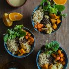 Lenten Bowls with Bulgur Wheat, Beluga Lentils, Roast Veggies and Honey Tahini Dressing www.thefoodiecorner.gr Photo description: Three bowls with the ingredients arranged side by side. All of them are on a wooden surface. Arranged around them are some wedges of orange and lemon. At the top of the photo is a bowl of dressing with a spoon sticking out of it. To the bottom of the photo is a saucer with some spices and herbs.