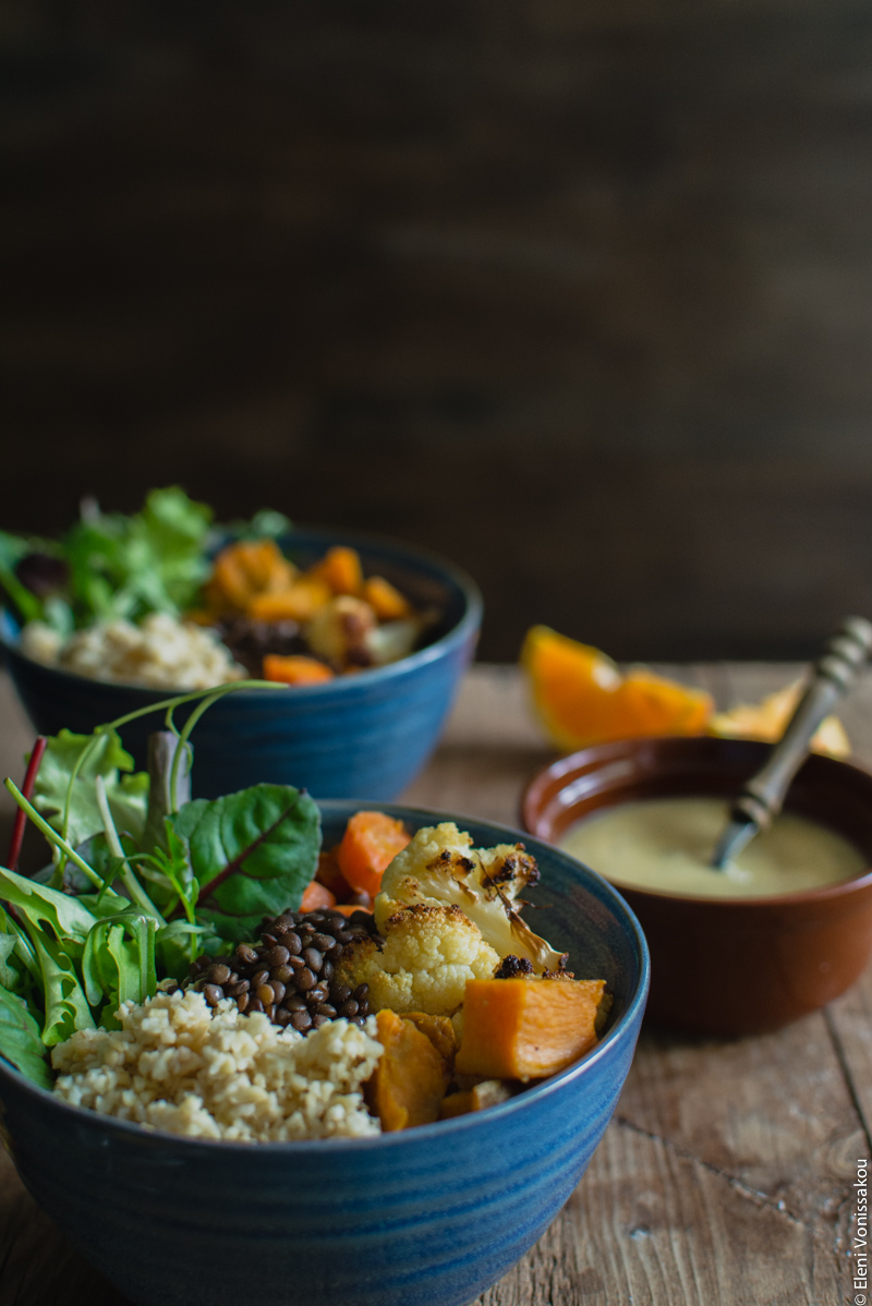Lenten Bowls with Bulgur Wheat, Beluga Lentils, Roast Veggies and Honey Tahini Dressing www.thefoodiecorner.gr Photo description: A side view of one of the bowls against a dark background. A second bowl is barely visible behind the first, as well as a small bowl of dressing.