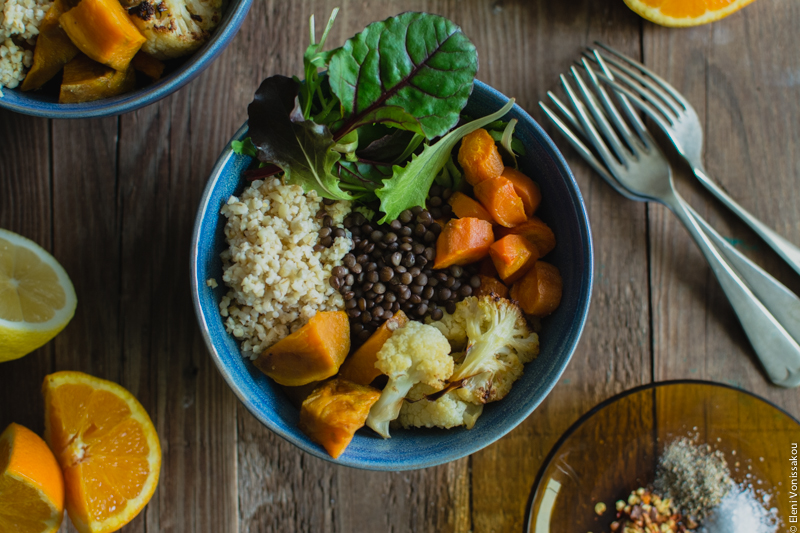 Lenten Bowls with Bulgur Wheat, Beluga Lentils, Roast Veggies and Honey Tahini Dressing www.thefoodiecorner.gr Photo description: A close view of one of the bowls filled with the ingredients side by side. Green salad leaves, carrots, cauliflower, sweet potato, bulgur wheat and lentils in the centre.
