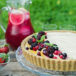Lemon Curd and Mascarpone Cheesecake with Berries www.thefoodiecorner.gr Photo description: A close look at half the cheesecake, sitting on a glass cake stand on a wooden box in a field. Red berries decorate the one side of the surface cheesecake. A few spearmint leaves are on top of the berries. In the background, a jug of pink lemonade on the box and long green grass behind that.