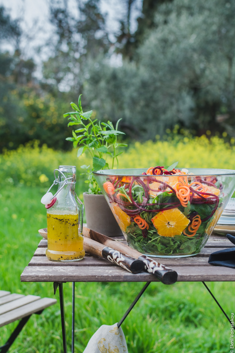 Spinach and Rocket Salad with Orange, Carrot and Raw Beetroot www.thefoodiecorner.gr Photo description: A side view of the table from a little further away. In the background some olive trees, very tall wild yellow flowers and lots of long lush grass.
