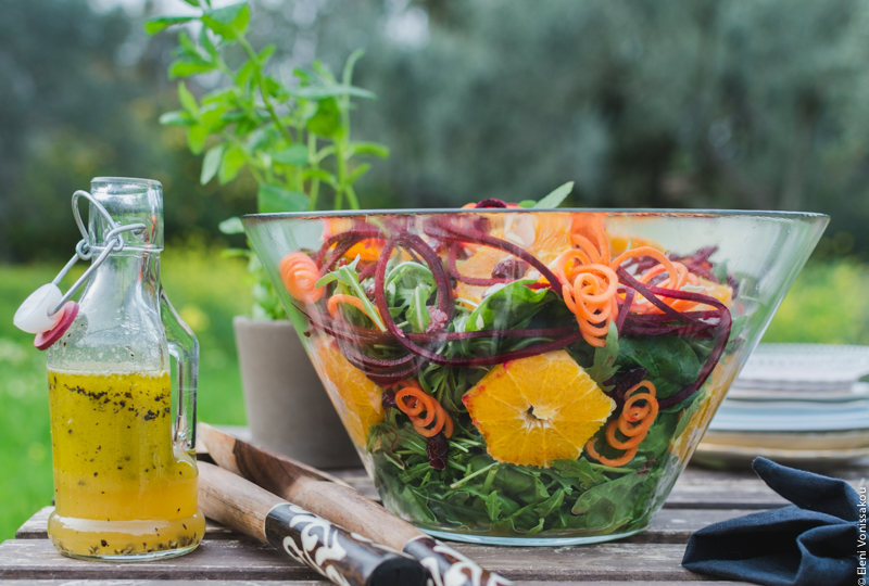 Spinach and Rocket Salad with Orange, Carrot and Raw Beetroot www.thefoodiecorner.gr Photo description: A side view of the large glass bowl of salad, with the contents visible. Flat against the side of the bowl are some star shaped slices of orange and some spirals of carrot. To the left of the bowl is a small bottle of dressing. In the background the small pot of spearmint, some trees and grass.