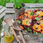 Spinach and Rocket Salad with Orange, Carrot and Raw Beetroot www.thefoodiecorner.gr Photo description: A large glass bowl of colorful salad (half visible) on a small wooden table located outside. On the table are a set of large wooden salad tongs with a pretty pattern on the bottom of the handles, a small bottle with salad dressing inside and a small pot with a spearmint plant. In the background and through the slats of the wooden table, one can see grass. The top of the salad is decorated with star shaped slices of orange, spiralized carrot, spiralized beetroot, almonds and spearmint leaves.