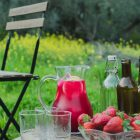 Homemade Pink Lemonade with Beetroot and Ginger www.thefoodiecorner.gr Photo description: A jug of dark pink lemonade with ice cubes and slices of lemon visible through the glass. The jug is on a wooden box set in a lush field with grass and flowers in the background. On the box are some bottles, empty glasses and a bowl of strawberries. To the left there is a wooden chair, half visible.