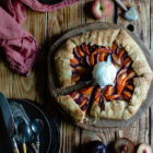 Easy Anthotyro Galette with Spiced Summer Fruit www.thefoodiecorner.gr Photo description: A galette with sliced peaches, apricots and plums, sitting on a round wooden cutting board in the centre of the photo and a little towards the right. One slice has been cut and is slightly pulled back from the galette. In the centre of the galette is a ball of vanilla ice cream. In the bottom left corner of the photo are some stacked plates with cutlery on top. Scattered on the wooden surface of the scene are halved stone fruits. In the top right corner a tiny bowl with honey and a honey wand. To the top left is a linen napkin.