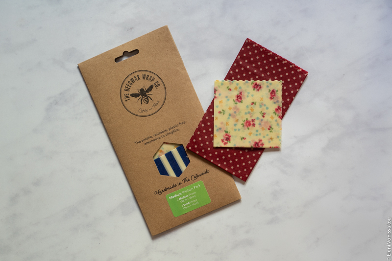 A packet of beeswax wraps and two more wraps lying on a marble surface.
