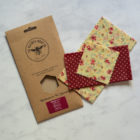 A cardboard packet and three beeswax wraps with a pretty pattern, lying on a marble surface.