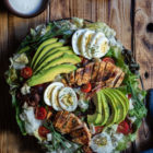 Chicken, Bacon, Avocado and Egg Salad with Gorgonzola Dressing (aka Cobb Salad) www.thefoodiecorner.gr Photo description: A large cobb salad on a platter, set on a wooden surface. To the top some wooden plates barely seen, with a few forks on top. Also to the top a small bowl of creamy dressing. To the bottom of the photo a tea towel made of a jeans-like fabric. The salad itself is decorated with slices of avocado spread out like a fan, sliced chicken breasts, clusters of bacon strips and overlapping slices of egg. Halved cherry tomatoes are dotted here and there.