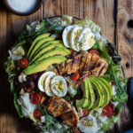 Σαλάτα Κόμπ (Cobb Salad) με Κοτόπουλο, Μπέικον και Ντρέσινγκ Γκοργκοντζόλας www.thefoodiecorner.gr Photo description: A large cobb salad on a platter, set on a wooden surface. To the top some wooden plates barely seen, with a few forks on top. Also to the top a small bowl of creamy dressing. To the bottom of the photo a tea towel made of a jeans-like fabric. The salad itself is decorated with slices of avocado spread out like a fan, sliced chicken breasts, clusters of bacon strips and overlapping slices of egg. Halved cherry tomatoes are dotted here and there.