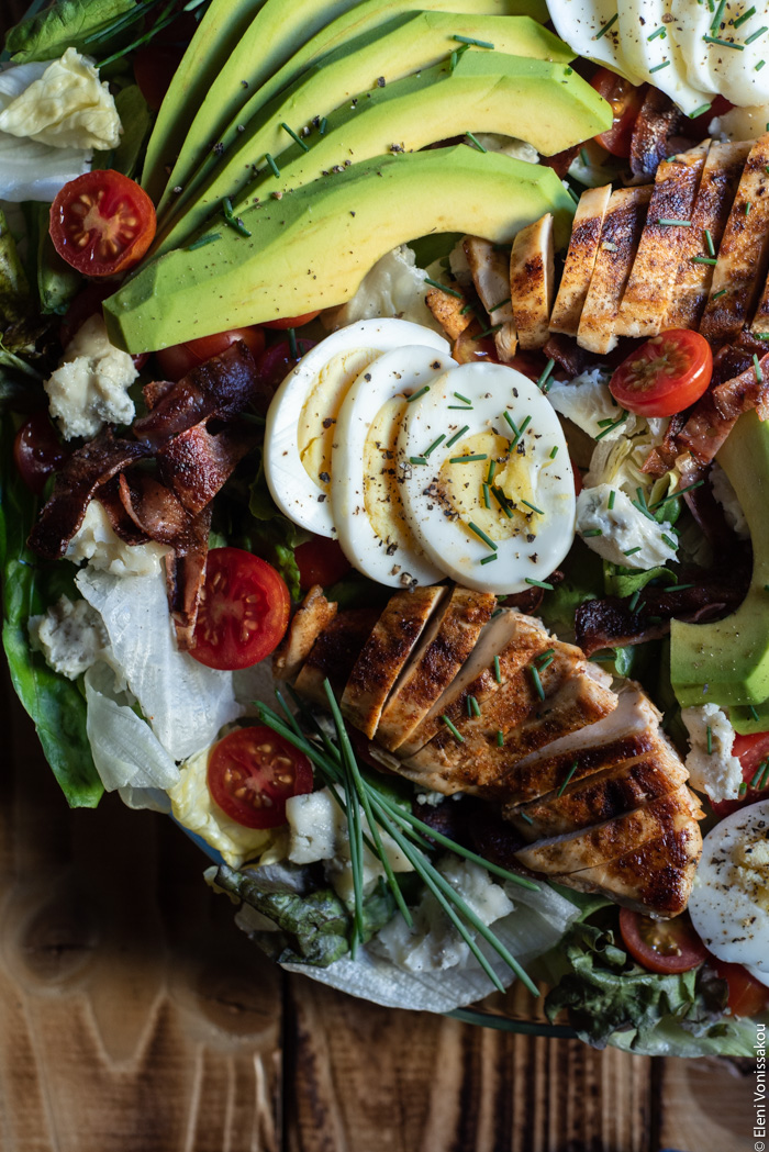 Σαλάτα Κόμπ (Cobb Salad) με Κοτόπουλο, Μπέικον και Ντρέσινγκ Γκοργκοντζόλας www.thefoodiecorner.gr Photo description: A close up of the cobb salad which is decorated with some chopped chives and cracked black pepper.