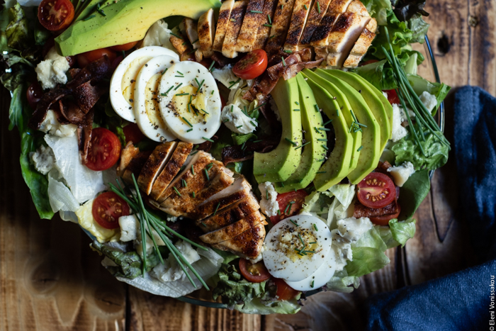 Σαλάτα Κόμπ (Cobb Salad) με Κοτόπουλο, Μπέικον και Ντρέσινγκ Γκοργκοντζόλας www.thefoodiecorner.gr Photo description: Another close up of the salad on the platter with the sliced chicken breast, avocado and egg lying on top. Cherry tomatoes are dotted here and there, and there are chopped chives sprinkled over the top.
