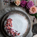 Almond Cardamom Rose Cake with Semolina and Olive Oil www.thefoodiecorner.gr Photo description: A top view of the cake, covered in icing sugar with one side decorated with chopped turkish delight and tiny dried rosebuds. The ceramic dish the cake is on, is sitting on wooly material. Around it, on the bare wooden surface are two vintage cake servers, some roses, and a small bowl of dried rosebuds.
