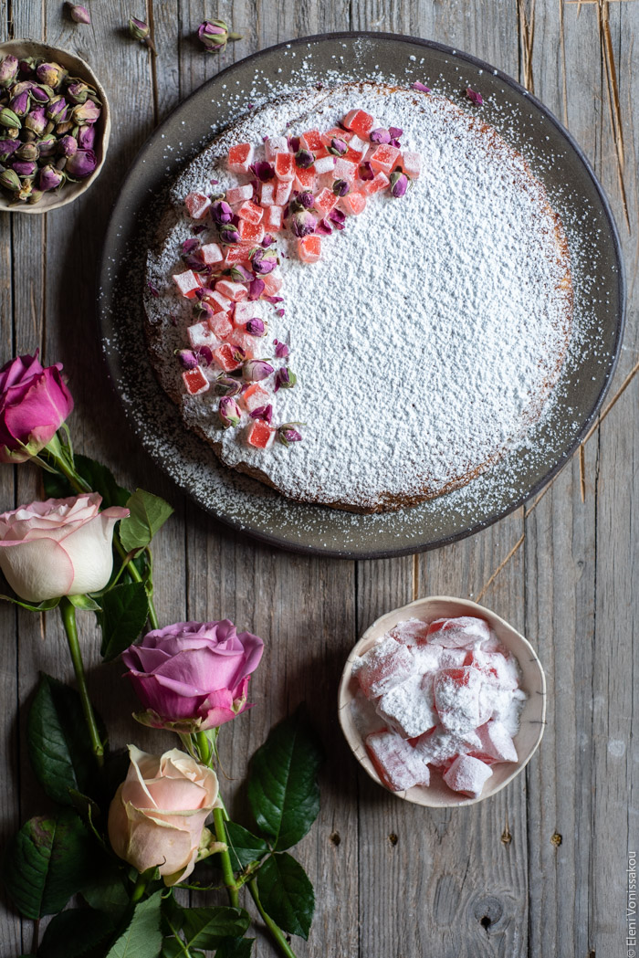 Almond Cardamom Rose Cake with Semolina and Olive Oil www.thefoodiecorner.gr Photo description: the cake in the top part of the photo. To the bottom are some roses and a small bowl of turkish delight.