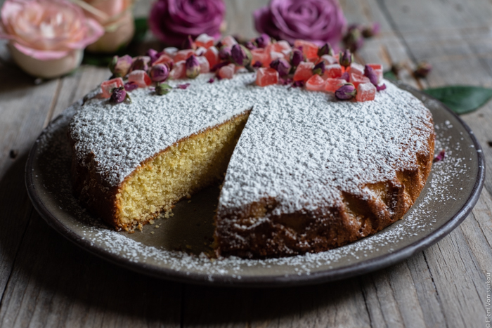 Almond Cardamom Rose Cake with Semolina and Olive Oil www.thefoodiecorner.gr Photo description: A side view of the cake. A slice has been cut so the inside of the cake is visible.