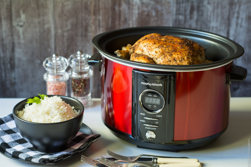 Βιβλίο Μαγειρικής Ελληνικές Συνταγές για Slow Cooker και Διαγωνισμός Giveaway www.thefoodiecorner.gr Photo description: Side view of a small slow cooker on a table with the top of a whole cooked chicken visible. To the side of the cooker is a small bowl of rice and salt and pepper mills.