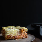 Slow Cooker Lasagna with Meat Sauce and Béchamel www.thefoodiecorner.gr Photo description: A side view of a delicious piece of lasagna, the meat and béchamel visible between the layers. The food is on a ceramic plate set against a dark background.