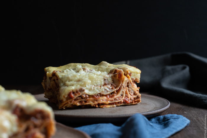 Slow Cooker Lasagna with Meat Sauce and Béchamel www.thefoodiecorner.gr Photo description: A side view of a piece of lasagna, the layers clearly visible with meat sauce and béchamel in between.