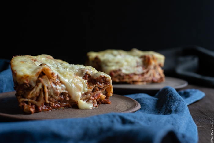 Slow Cooker Lasagna with Meat Sauce and Béchamel www.thefoodiecorner.gr Photo description: A side view of two pieces of lasagna, one of them with a bit of melted cheese oozing down the side. In front of the plates is a blue denim style napkin.