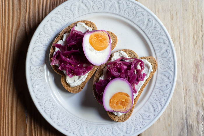Quick Pickled Eggs and Red Cabbage www.thefoodiecorner.gr Photo description: A plate with two wheat rusks topped with soft white cheese, pickled cabbage and pickled egg halves.