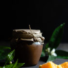 Εύκολη Κρέμα Σοκολάτα Πορτοκάλι www.thefoodiecorner.gr Photo description: A jar of chocolate orange curd with a paper cover over the lid secured with string. In the foreground, some pieces of orange and some leaves from an orange tree. In the background, some more leaves with orange blossoms.