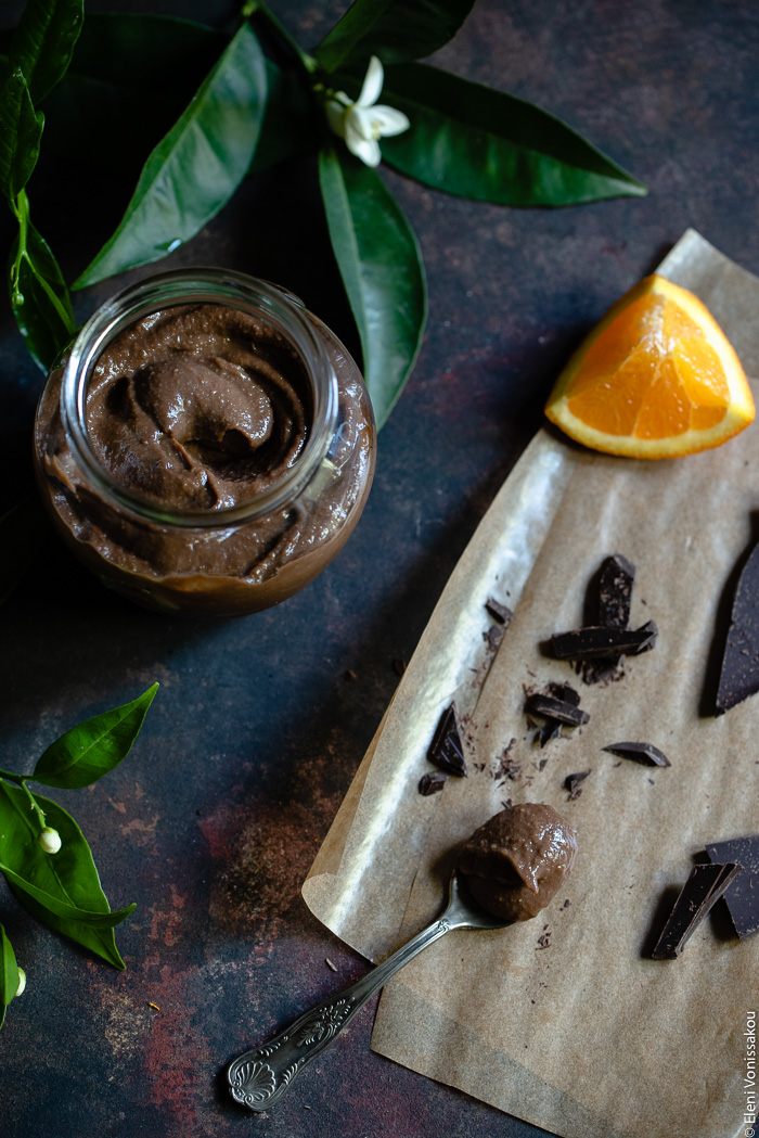 Chocolate Orange Curd – The Easy Way www.thefoodiecorner.gr Photo description: An open jar of chocolate orange curd in the top left corner, next to some orange leaves. To the right are some pieces of chocolate and orange, lying on grease-proof paper. Among the pieces is a spoon full of curd.