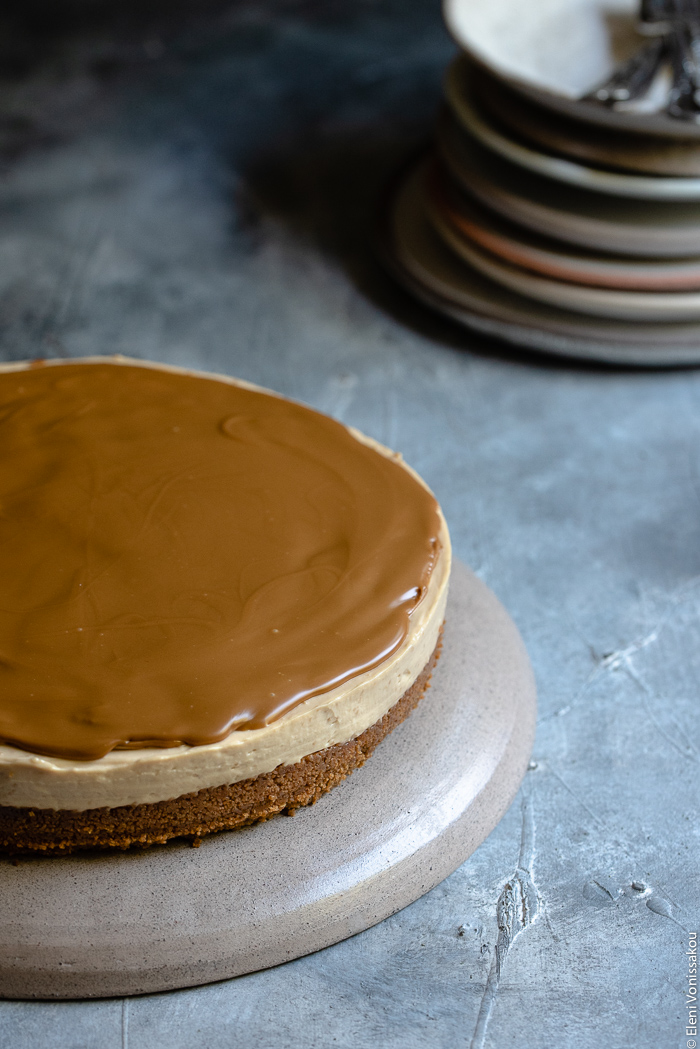 Easy Speculoos Cheesecake www.thefoodiecorner.gr Photo description: A whole speculoos cheesecake with a layer of melted speculoos spread on top. In the background is a stack of ceramic plates.
