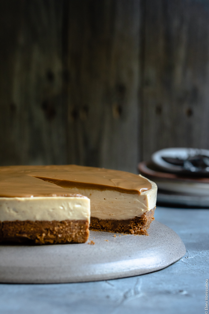Easy Speculoos Cheesecake www.thefoodiecorner.gr Photo description: a side view of a speculoos cheesecake with one slice missing.