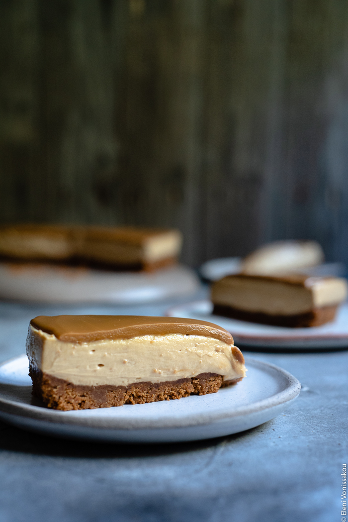 Easy Speculoos Cheesecake www.thefoodiecorner.gr Photo description: A side view of a slice of cheesecake, the three layers (biscuit base, creamy filling and melted speculoos) clearly visible.